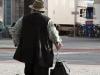 BRD, 2010-09-11, Featurefoto fur Armut, armlich, Konsum; im Bild (v.l.n.r.): Ein armlich anmutender Stra?enmusiker steht mit seiner Harmonika und einem Koffer am Stra?enrand, dahinter das Logo